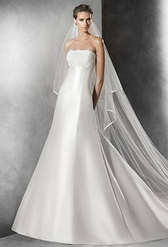 Pronovias. Strapless A-line mikado silk dress. Lace around bust and back buttons to the hem. Lace and guipure jacket with off-the-shoulder neckline and elbow-length sleeves.