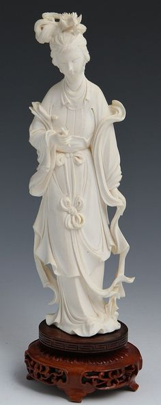 CHINESE CARVED IVORY BEAUTY WITH BASE Chinese carved ivory female beauty figurine; elaborately dressed with flowing robes and figural hair ornament. Attached with pegs to wooden base. Weight: 346.6g with base Size: 10.25 with base
