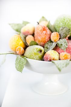 sugared fruit for the center piece with a single white candle in one of the old bronze candle holders?