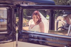 Red head bride arrives in classic wedding car at Highcliffe Castle wedding venue. Photography by one thousand words wedding photographers
