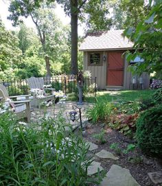 With a relaxing patio, an inviting birdhouse, and a cozy cover of foliage, this little garden space could not be more peaceful.