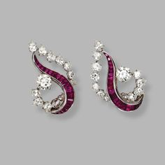 PAIR OF PLATINUM, DIAMOND AND RUBY EARCLIPS, CIRCA 1960. Of free form design set in the center with curved lines of calibré-cut rubies, accented by round diamonds weighing approximately 2.40 carats, and pear-shaped diamonds weighing approximately 3.10 carats.
