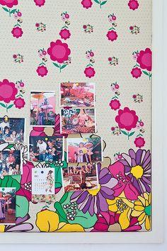Ainda no quarto de Bertha, painéis de madeira revestidos com tecidos divertidos recebem as fotos preferidas da menina