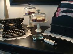 "I just love what a bit of black paint can do to update an ""out-of-style"" piece of furniture. ... and the old black typewriter, letter organizer, ivory-tone magnifying glass, & pedestal cake plates under crystal clear cloches are just the right touch on this desk too! Yum! Are those cupcakes for real?! ;)"