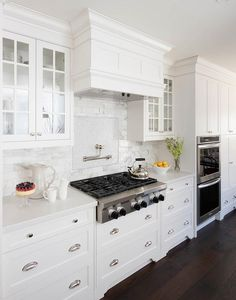 Gorgeous white, paneled kitchen hood flanked by white china cabinets hangs over a polished nickel, swing arm pot filler and a stainless steel cooktop atop pot and pan drawers against a gray mosaic cooktop backsplash framed with white marble tiles.