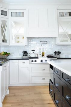 Beautiful black and white kitchen features mirrored upper cabinets with x trim and white shaker lower cabinets paired with black quartz countertops and a marble tiled backsplash.