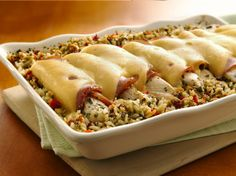 Ham-stuffed chicken rolls topped with Swiss cheese rest on a bed of flavored rice, resulting in a hearty main dish.