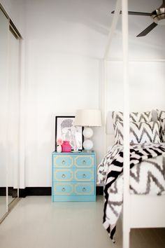 Bright, graphic bedroom with blue nightstand
