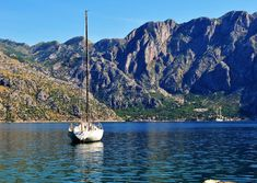 Photo about Photo of Kotor bay with cristal water a boat and a blue sky behind the mountains - Kotor Bay - Montenegro - July 2010. Image of mountains, water, montenegro - 113952020