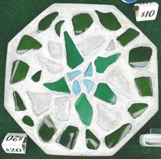 """This 12"""" solid concrete octagon garden accent has dark green tumbled glass, light green tumbled glass, light blue tumbled glass and clear tumbled glass with ridges on it. It weighs about 14lbs and is sprayed with acrylic UV protectant spray and brushed with low gloss acrylic concrete sealer. 