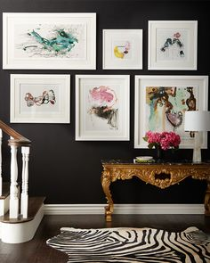 Glam gallery. White frames are a stylish contrast against a black wall.