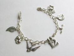 Katniss Charm Bracelet - The nine charms on this bracelet symbolize her life before, during and after the arena: a Mockingjay, girl on fire, 12, Arrow, The kitten Buttercup (a symbol for Prim), a Leaf - for the trees Katniss hides in and hunts from, and Two hearts - for Peeta and Gale. I really like this bracelet too.