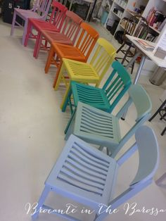 A pretty rainbow of painted chairs, waiting to go to a party hire job.  Chalk Paint ™ decorative paint by Annie Sloan colours from top:  Henrietta, a mix of Emperor's Silk and Old White, Scandanavian Pink, Barcelona Orange, English Yellow, Florence, Duck Egg, and Louis Blue.