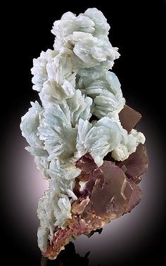 Barite crystals stacked atop purple Fluorite