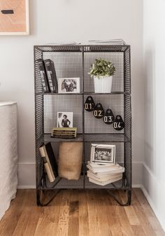 Urban Outfitters industrial shelving unit styled with vintage books, number hooks and plant.