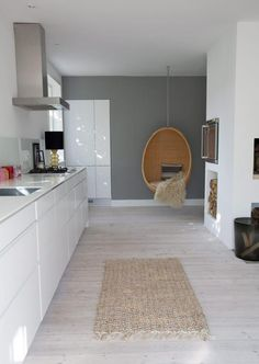 White kitchen + light wooden floors + grey wall