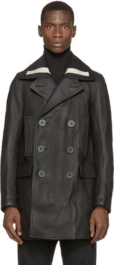 Long sleeve leather peacoat in black. Textile trim in black and beige at peaked lapel collar. Double-breasted button closure and flap pockets at front. Five-button surgeon's cuffs. Vented at back hem. Zippered pockets at fully lined interior. Tonal stitching.