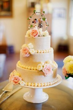 simple three tiered wedding cake with fresh flowers and a handmade cake topper
