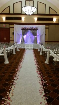 Hues of purple and silver ceremony decor.