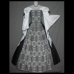 The black and white patterning coupled with the white sleeves and black over skirt make this truly stunning!