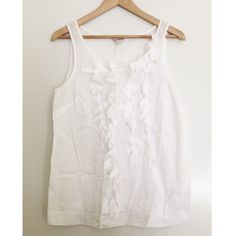 J. Crew White Cotton Ruffle Tank This tank by J. Crew has a fun ruffle design going down the front & in great condition. Pair this with a colorful cardi & some jeans to complete the outfit. 100% cotton & has zipper on the side. J. Crew Tops Blouses