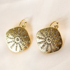 For a golden shine and sparkle that complements any outfit, pick up a pair of Gold and Stones Sand Dollar Earrings.