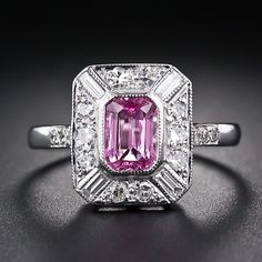 A brilliant bubble gum pink emerald-cut sapphire is showcased in classic Art Deco fashion in this charming and cheerful ring, crafted in bright 18 karat white gold and enlivened with a straight baguette diamond on each corner and sparkling single-cut diamonds in between. Late twentieth century