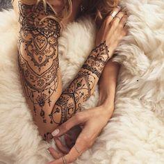 Frau mit schöner Armtattoo in Schwarz, viele kleine Elemente, florale Akzente, weiße Decke, Ringe
