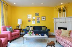 I would've never considered a yellow this deep until I saw this. Love the arrangement of the artwork and the symmetry of the pink chairs and loveseat.