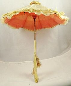 A lovely late 1850s silk parasol, ivory silk with fine ivory silk fringe trim on the bonnet and soft coral silk lining.  The handle is bone carved with a serpent like creature.