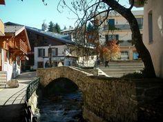 Megève: Ponte di pietra che attraversa il fiume, negozi e case nel villaggio (stazione di sport invernali ed estivi) - France-Voyage.com