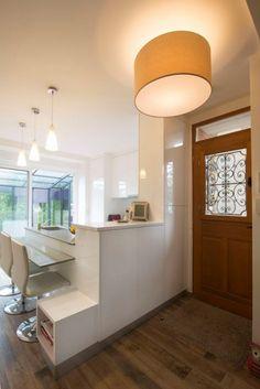 Une cuisine blanche moderne ouverte sur l'entrée