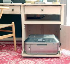 A spot we often all get stuck when organizing and decorating an office or work space - what do you do with that bulky printer? As computers have slimmed down printers sure haven't. Here are a few tips and tricks to keep your overbearing hunk of plastic from being the focal point of your workspace.
