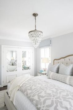 A Pottery Barn Clarissa Crystal Drop Small Round Chandelier illuminates a white and gray bedroom furnished with a French tufted bed dressed in white and gray bedding topped with a gray lumbar pillow placed in front of silver shams. - May 11 2019 at Pale Blue Bedrooms, White And Silver Bedroom, Grey And White Bedding, Blue Gray Bedroom, Grey Bedding, Bedroom Colors, Luxury Bedding, Bedding Sets, Small Grey Bedroom