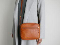 Hochwertige Schultertasche aus Rindsleder in Cognacbraun mit goldenen Reißverschlüssen.  Diese mittelgroße Handtasche ist der perfekte Begleiter für Tag und Nacht.  - Federleicht und mit...