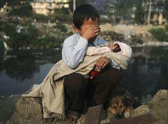 """""""Treuer Freund"""" - Ein weinender Junge hält nach Zusammenstößen von Hausbesetzern in Nepals Hauptstadt Kathmandu mit der Polizei seine kleine Schwester auf dem Schoß. Sein Hund liegt ihm zur Seite."""