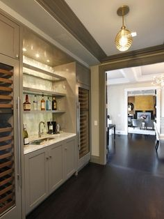 Park Avenue Penthouse - Fabulous wet bar design featuring twin glass-front wine fridges flanked by gray cabinets with white marble countertop and stacked gray shelves.