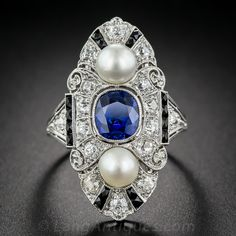 Natural Sapphire, Diamond, Natural Pearl Art Deco Dinner Ring.  Singular and sensational, from the zenith of the Jazz Age - circa 1925 - a sublime and stunning, 1 and 1/8 inch long, original Art Deco dinner ring in pristine condition. A vibrant, royal blue no-heat, natural cushion-cut sapphire, weighing just under 2 carats, shares center stage with a lustrous pair of natural pearls set atop a sparkling, diamond studded platinum plaque, designed in three sections and accented with streaks of…