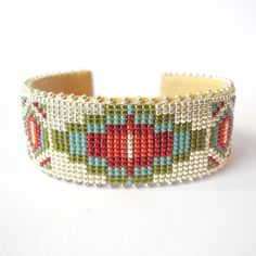 This cuff was made by a collective of Navajo beaders based out of New Mexico, and features glass seed beads in neutral colors and a geometric Navaj...