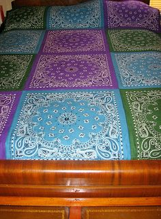 I used big, colorful bandanas to construct this lighter weight quilt, made with a thinner, traditional batting.  It is shown here on a full size bed.  It is tied in 5 places on each square, including once in each center with a button.