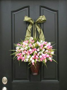 I like this. Different from a traditional wreath, but with the same sweet tulips.    ST note to self: Use the old metal wall container as a front door decoration