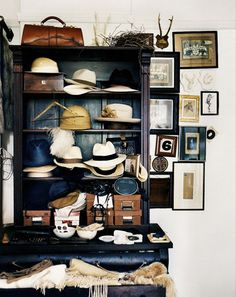 A painted cabinet full of fedoras and hats.