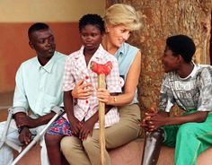 Holding an amputee child in her lap, Princess Diana meets victims of landmines - a legacy of Angola's twenty-year civil war - at a rehabilitation centre in Huambo, Angola. The Princess was a leading supporter of the Red Cross campaign to ban landmines. (© Reuters/Corbis)
