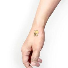 Tiny Woodstock bird tattoo on the hand.