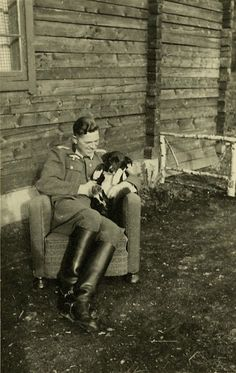 German soldier playing with a dog.,.