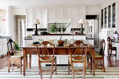 """The kitchen is the hub of the house, with room for a desk and a big breakfast table. """"I thought the more formal 18th-century lyre-back chairs combined with the 19th-century French farmhouse table was an interesting juxtaposition,"""" designer Connie Newberry says. The high back of the banquette hides any mess on the mahogany-topped island. A pair of lamps by Vaughan """"makes it feel more like a room and less of a kitchen."""" The cabinetry is painted in her favorite creamy white, Benjamin Moore's Linen White.   - HouseBeautiful.com"""