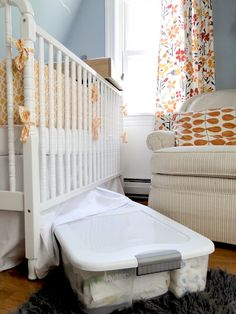 Extra crib sheets and other bedding stored under the crib in lidded bin