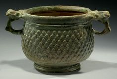 Roman green glazed pottery skyphos, 1st century A.D. With two ring handles surmounted by a molded thumbpiece, the body has relief decorations in the form of pine cone scales and covered with a silvery iridescence, ochre glazed interior, 9 cm high. Private collection