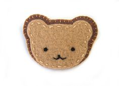 This cute bear wants to go home with you! This pin in in the shape of a friendly, smiling teddy bear. Its made of soft wool-blend felt in shades of