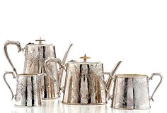 The four-piece silver-plate beverage set, made in England c. 1865, is engraved with elaborate fern motifs. The lids of the teapot and coffee pot boast ivory finials.